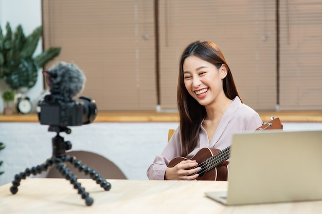 Young asian woman playing and teaching guitar online while record by camera