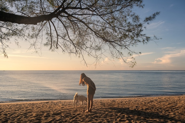 Young asian woman playing with dog under the tree on the beach in tropical sea at vacation