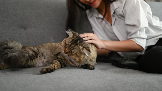Young asian woman playing with her cat