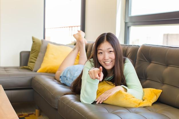 Молодая азиатская женщина, указывая на камеру с довольной, уверенной, дружелюбной улыбкой, выбирает вас