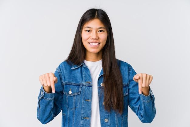Молодая азиатская женщина указывает вниз с пальцами, положительным чувством.