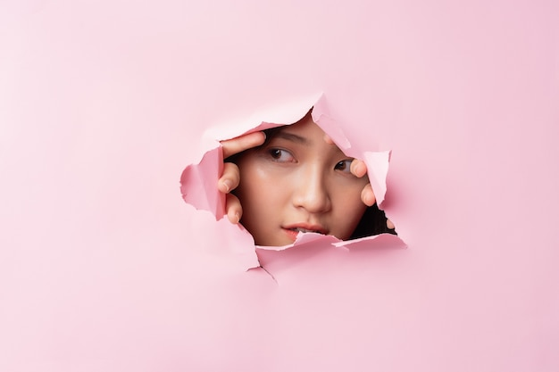 Young asian woman poked her head through the torn paper