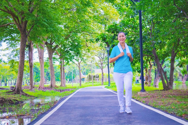Young asian woman portrait. she is jogging in park. she is  smile and be happy in good time