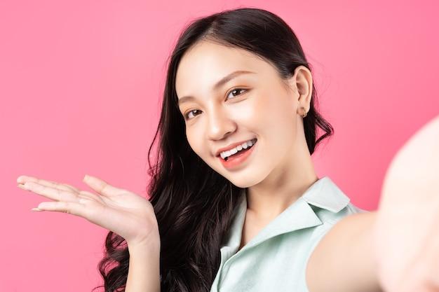 ピンクのselfieのポーズをとる若いアジアの女性