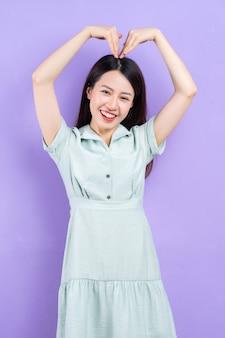 Молодая азиатская женщина позирует на фиолетовом фоне