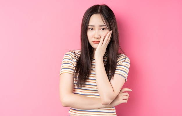 Young asian woman posing on pink