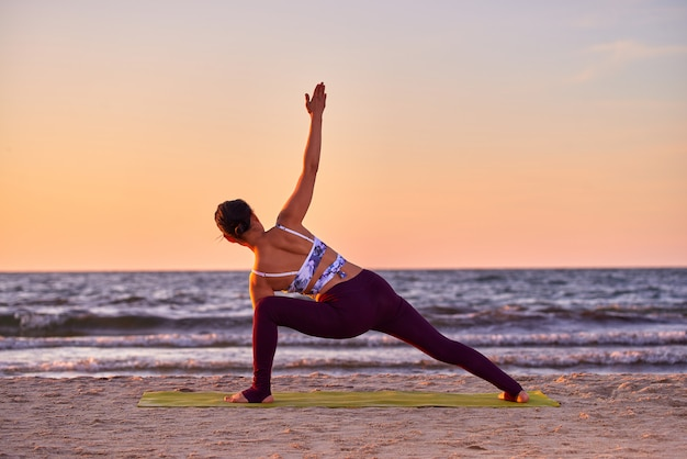 Young asian woman practicing yoga, doing exercise, working out by the sea, wearing sportswear, pants and top