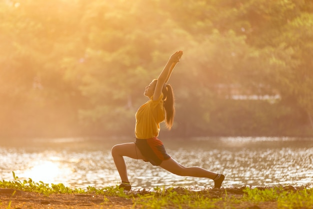 Young asian woman practicing yoga warrior pose near lake at sunset time