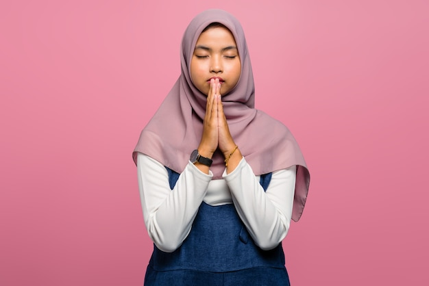 Young asian woman praying with folded hand