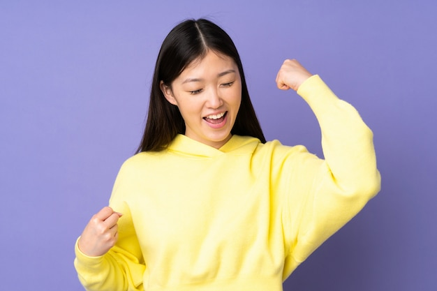 Young asian woman on purple wall celebrating a victory