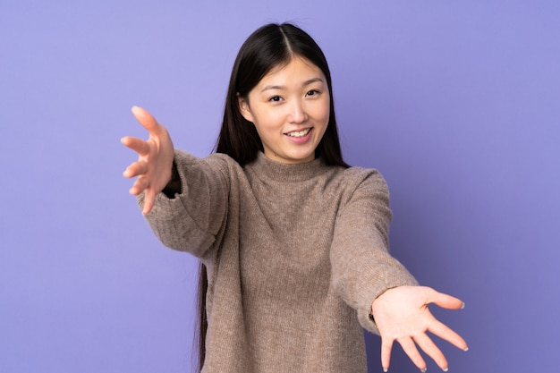Young asian woman on purple wall presenting and inviting to come with hand