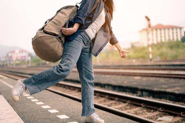 젊은 아시아 여성이 철도 플랫폼에서 기차를 흔들기 위해 손을 들어 올립니다. 관광, 여행 및 레크리에이션의 개념입니다.