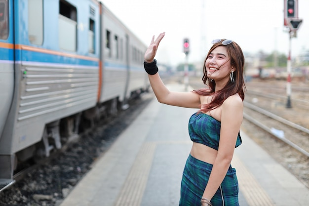 Young asian woman raising hand to someone in train station with smiling face