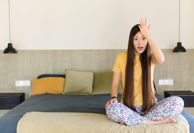 Young asian woman raising palm to forehead thinking oops, after making a stupid mistake or remembering, feeling dumb