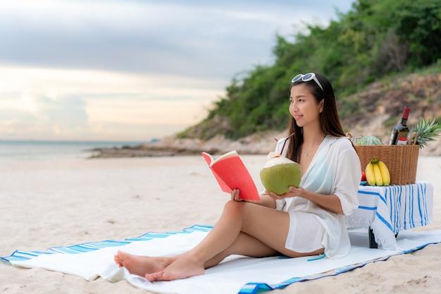 Молодая азиатская женщина читая книгу