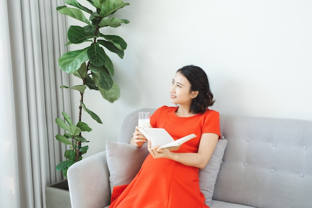 Young asian woman reading book relaxing at sofa and drinking milk.