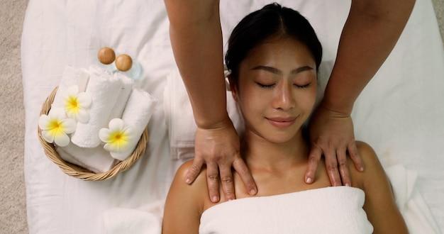 Молодая азиатская женщина получает массаж плеч в спа-салоне профессиональной массажисткой