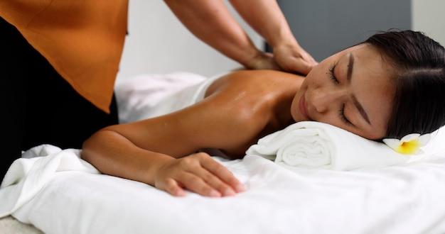 Молодая азиатская женщина получает масляный массаж спины в спа-салоне от профессиональной массажистки