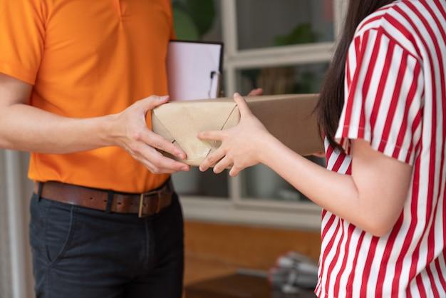 Молодая азиатская женщина получая коробку пакета от работника доставляющего покупки на дом в оранжевой форме на ее доме. курьерская служба.