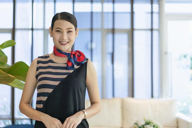 若いアジア人女性の受付係がホテルでお客様をお迎えするために笑顔で立っています。