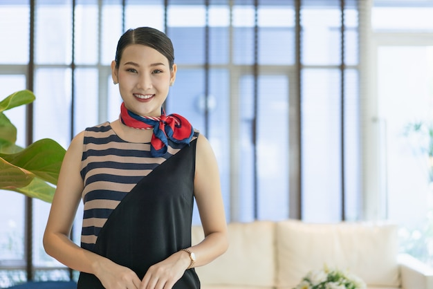 Young asian woman receptionist stands smiling to welcome customers at the hotel.