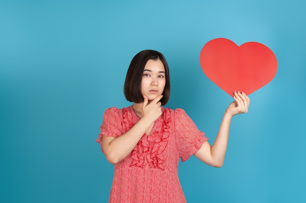 Young asian woman in a red dress holds a large red paper heart in her hands