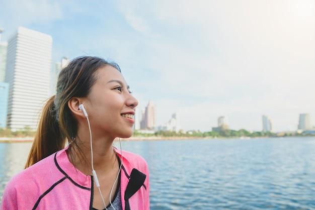 젊은 아시아 여자는 도시 실행 후 음악을 듣고 자신을 휴식