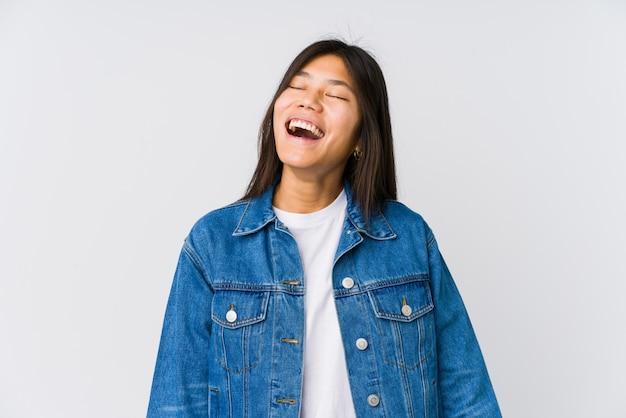 Молодая азиатская женщина ослабила и счастливый смеяться над, шея протянула показывать зубы.