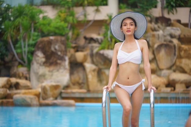 スイミングプールでリラックスした若いアジア女性