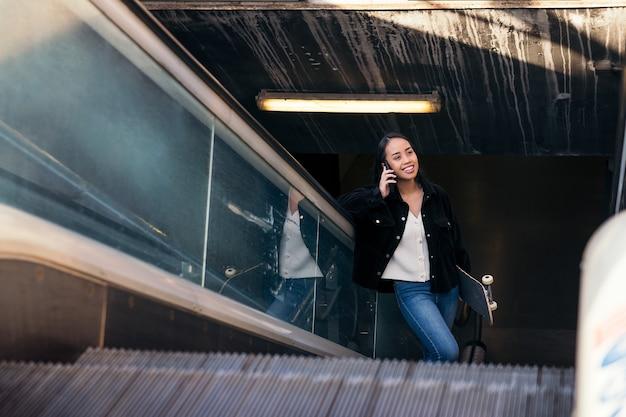 젊은 아시아 여성이 지하철 역에서 스케이트보드를 들고 에스컬레이터를 타고 전화 통화를 한다