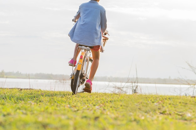 Young asian woman riding bicycle at park with sunset
