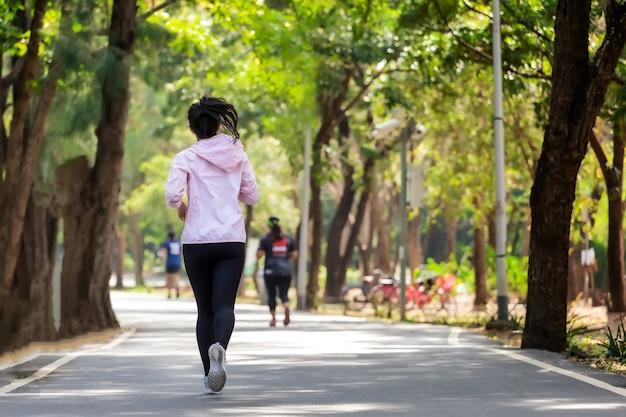 Молодая азиатская женщина в парке на улице в спортивной одежде.