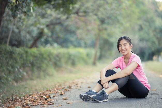 靴ひもを結ぶ若いアジアの女性ランナー、ライフスタイルフィットネスとアクティブな女性は、都市のコンセプトで運動します。