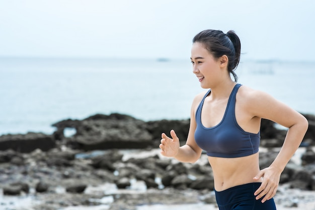 Young asian woman running on the beach. girl jogging workout in seaside