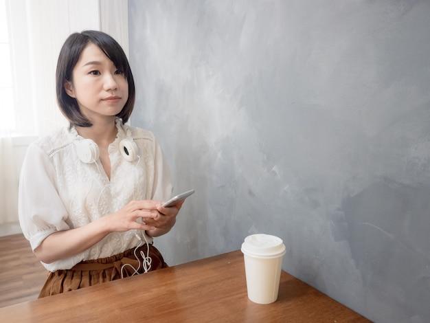 휴대 전화를 들고 젊은 아시아 여자의 손