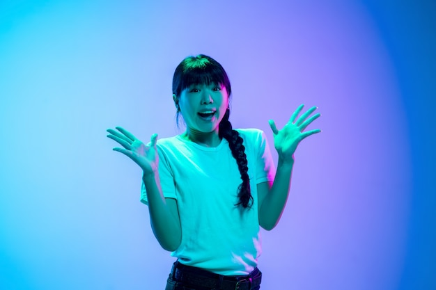 Young asian woman's portrait on gradient blue-purple studio background in neon light. concept of youth, human emotions, facial expression, sales, ad. beautiful brunette model.