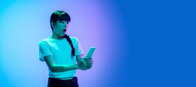 네온 불빛에 그라데이션 파란색 보라색 스튜디오 배경에 젊은 아시아 여자의 초상화. 청소년, 인간의 감정, 표정, 판매, 광고의 개념. 아름다운 갈색 머리 모델. 전단
