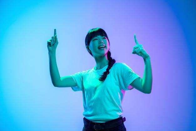 네온 불빛에 그라데이션 파란색 보라색 스튜디오 배경에 젊은 아시아 여자의 초상화. 청소년, 인간의 감정, 표정, 판매, 광고의 개념. 아름다운 갈색 머리 모델.