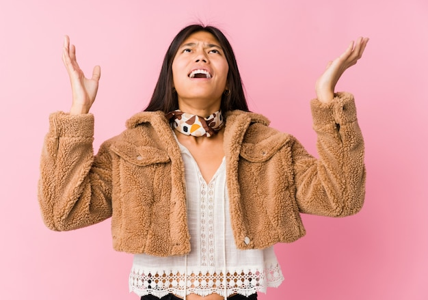 Young asian woman screaming to the sky, looking up, frustrated.