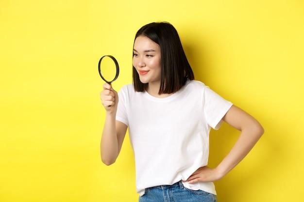 젊은 아시아 여자 뭔가를 검색, 돋보기를 통해 왼쪽 찾고 기쁘게 미소, 조사, 노란색 배경 위에 서.