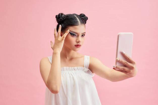 ピンクの背景に携帯電話で若いアジアの女性selfie