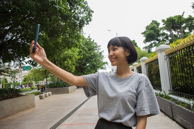 Young asian woman selfie with mobile phone  in public spaces