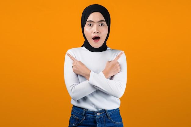 若いアジアの女性はショックを受け、黄色の背景を指しています
