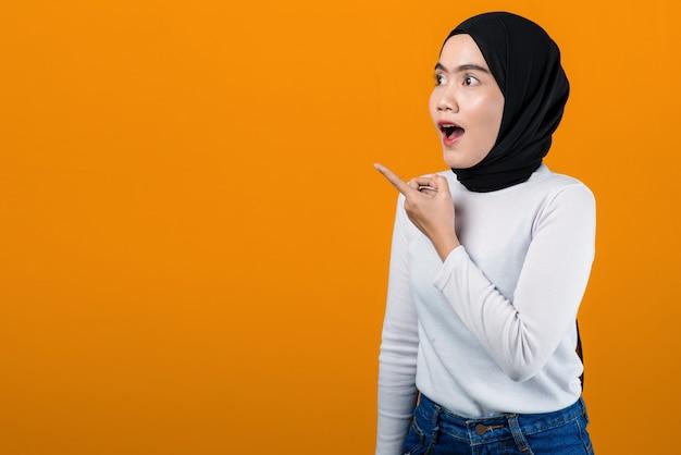Молодая азиатская женщина в шоке и указывая на пустое пространство