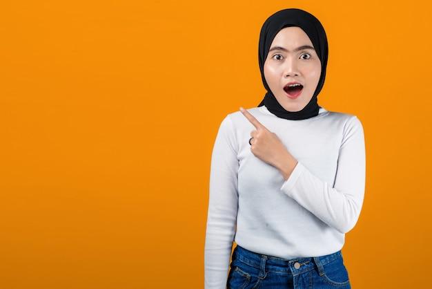 若いアジアの女性はショックを受け、空のスペースを指しています