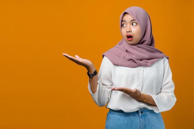 Молодая азиатская женщина шокирована и показывает продукт
