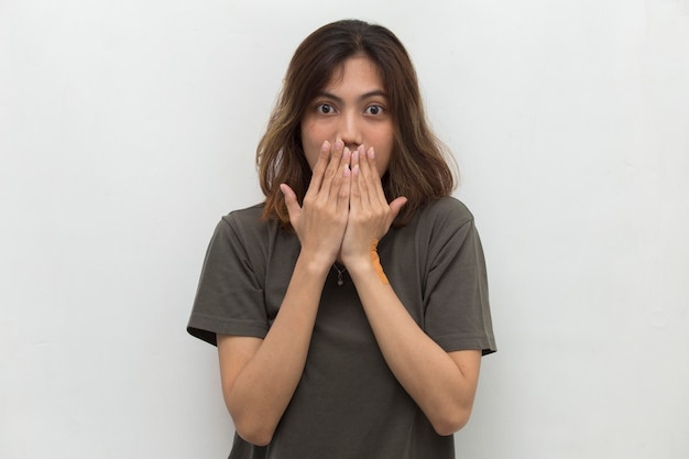 Young asian woman shocked covering mouth with hands for mistake secret concept