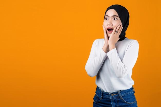 黄色の背景にショックを受けた若いアジアの女性
