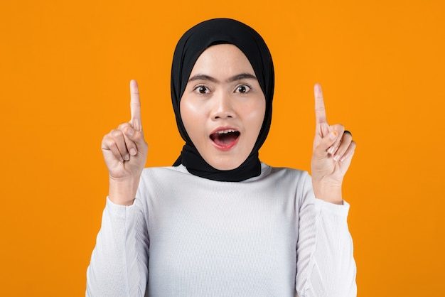 Young asian woman shocked and pointing up
