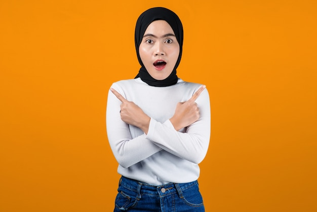 Young asian woman shocked and pointing on yellow background